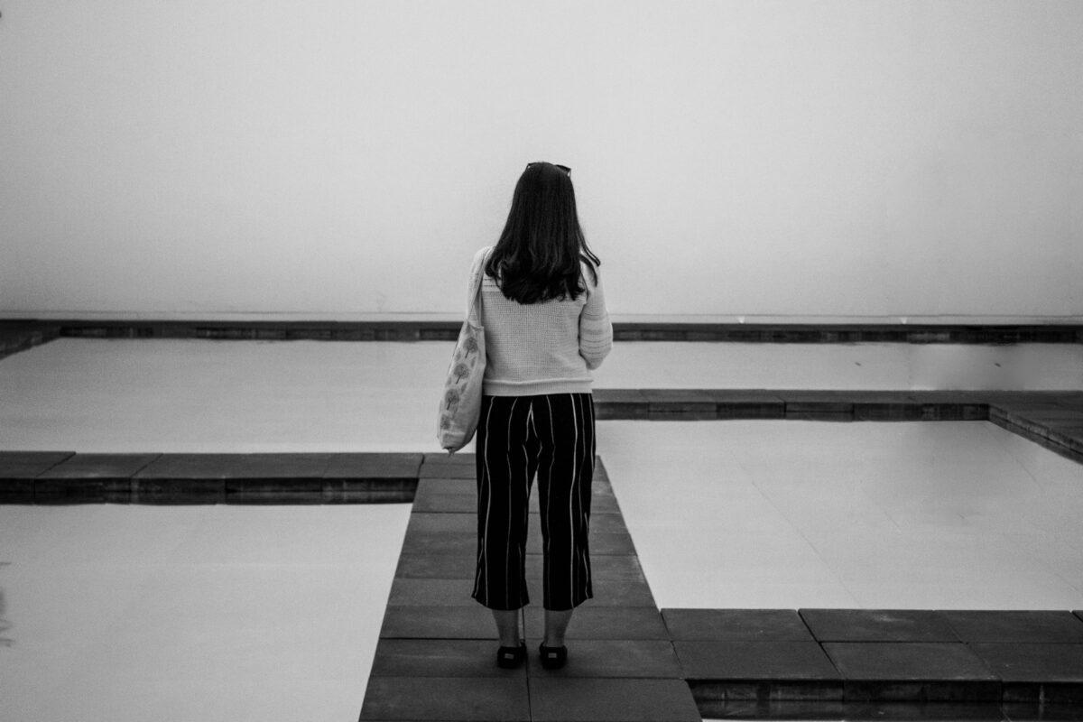Frau, von hinten fotografiert, alleine auf Steg am Meer